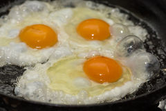 Three eggs frying in the hot oil Royalty Free Stock Photography