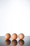 Three eggs on glass table Stock Images