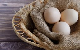 Three eggs lie on a sackcloth in a wicker basket. stock image