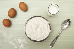 Three eggs milk flour prepared on table for making dough. Three eggs and milk flour prepared on table for making dough Stock Photos