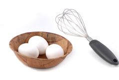 Three Eggs Omelet. Three white-shelled eggs in a wooden bowl, with whisk beside bowl. Isolated on white background Royalty Free Stock Photos