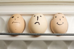 Three eggs painted with human faces Stock Photography