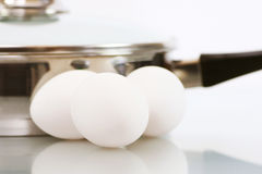 Three Eggs and a Pan. Three white chicken eggs with a small stainless steel pan on white Stock Photography