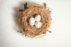 Three eggs with red spots in a hay nest. Easter Holiday. Three painted eggs with red spots in a hay nest. Easter Holiday. Top view royalty free stock photos