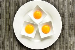 Three eggs. In small bowls on a plate Royalty Free Stock Image