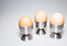 Three eggs in the stands on isolated white Royalty Free Stock Photos