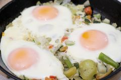 Three eggs with vegatables on frying pan stock images