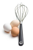 Three eggs and whisk Royalty Free Stock Image