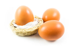 Three eggs in white background. Three eggs in a white background with a small bamboo basket Stock Photos