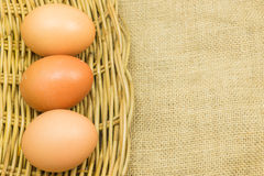 Three eggs in wicker basket on gunny sack background Stock Photo