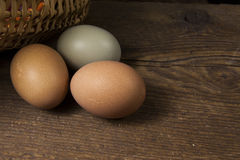 Three eggs and a wicker basket. Three organic chicken eggs with a rustic wooden background and wicker basket Royalty Free Stock Image
