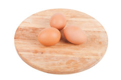 Three eggs on a wooden board isolated on white background Royalty Free Stock Photo