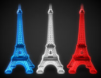 Three Eiffel towers glow in French flag colors. On a black background Stock Photos