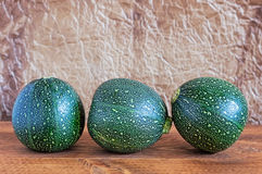 Three Eight Ball Squashes. On a wooden table with brown wrinkled parchment paper background Royalty Free Stock Images