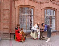 Three elderly people in medieval costumes depict artisans at the festival. Three elderly people in medieval costumes depict artisans at a festival in the city of stock photos