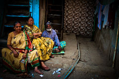 Three elderly people at rest in the Dharavi Slums in Mumbai Indi Royalty Free Stock Image