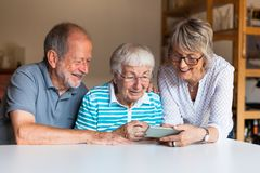 Three elderly persons using smart phone. Three elderly persons using a smart phone at home, sitting on a table, smiling stock photo