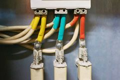 Three electrical high-voltage fuses connected to the colored wires. Industrial background. stock image