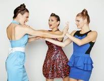 Three elegant fashion woman fighting on white background. Three elegant fashion women fighting on white background, bright dresses Royalty Free Stock Images