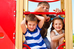 Three elementary aged children. In the playground Stock Images
