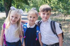 Three elementary school students with backpacks. On the street Stock Image