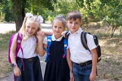Three elementary school students with backpacks. On the street royalty free stock photos