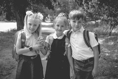 Three elementary school students with backpacks. On the street. Monochrome photo royalty free stock image
