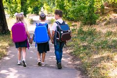 Three elementary school students with backpacks. Walking along the sidewalk royalty free stock photos
