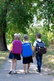 Three elementary school students with backpacks. Walking along the sidewalk royalty free stock photo