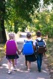 Three elementary school students with backpacks. Walking along the sidewalk stock image