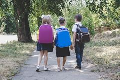 Three elementary school students with backpacks. Walking along the sidewalk royalty free stock images