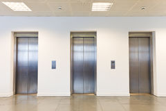 Three elevators in office building Stock Images