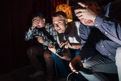 Three emotional guys play video game, competition Royalty Free Stock Images