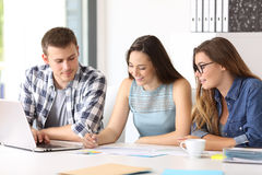 Three employees coworking at office. Three happy employees coworking reading documents at office royalty free stock photos