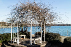 Three empty benches in a waterfront gazebo. With open metal frame and trailing deciduous creeper overlooking a calm ocean on a sunny day Royalty Free Stock Image