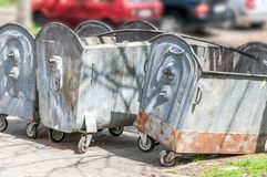Three empty big metal dumpster cans for garbage and junk on the street to collect litter and prevent city from pollution.  Stock Photo