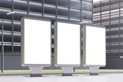 Three empty billboards, side. Side view of three glowing empty billboards standing in a street near an office building. 3d rendering, mock up Royalty Free Stock Images
