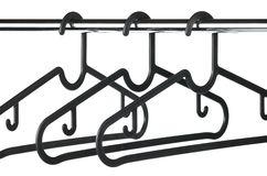 Three empty black coat hangers / clothes hangers on a clothes rail Royalty Free Stock Photography