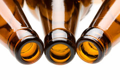 Three empty bottles over white. Close-up of the brown glass bottle necks Stock Image