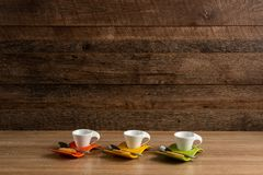 Three empty coffee cups with biscuit and teaspoon nearby stock image
