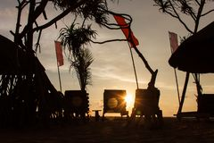 Three empty deck chair silhouettes at sunset beach, red flags waving stock image