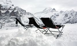 Three empty deckchairs on top of the mountains. Stock Images