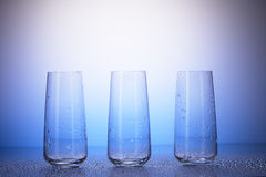 Three empty drinking glasses in drops of water Royalty Free Stock Photography