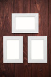 Three empty frames on brown wooden desk Stock Photography