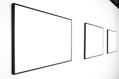 Three empty frames on white wall royalty free stock image