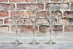 Three empty glass goblets on a rustic wooden board Royalty Free Stock Photography