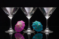 Three empty glasses of champagne with paper umbrellas Royalty Free Stock Images