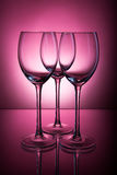 Three empty glasses on a dark burgundy background Royalty Free Stock Photo