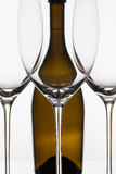 Three empty glasses of wine and brown bottle Stock Images