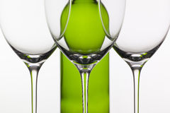 Three empty glasses of wine and green bottle Stock Images